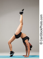 Beautiful sporty girl standing in acrobat pose or yoga asana...