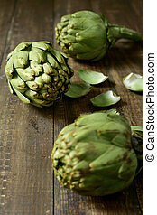raw artichokes on a wooden surface - closeup of some raw...