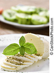 sliced fresh cheese in a plate - closeup of a plate with a...