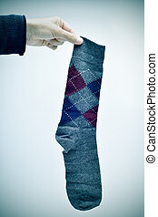 man holding an argyle patterned sock, vignetted - closeup of...