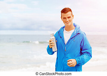 Man drinking from a sports bottle - Young man in sport wear...