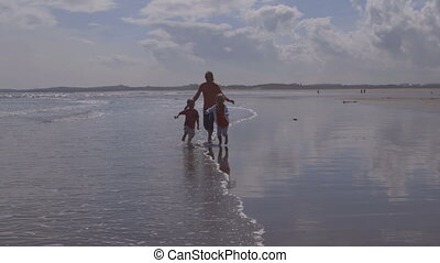 Fun by the sea - A happy young family of three laugh and...