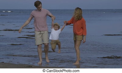 Sunny seaside fun - A happy little boy walks hand in hand...