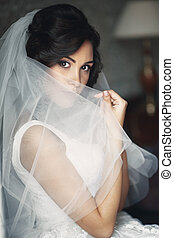 Sexy relaxed brunette bride hiding behind veil near white window closeup