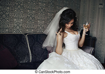 Sexy brunette bride in white dress with champagne glass...