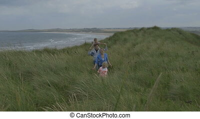 Family in the dunes - A happy young family laugh and smile...