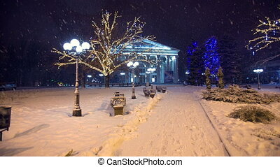 Christmas Eve In The City Park - Snow falls in a christmass...