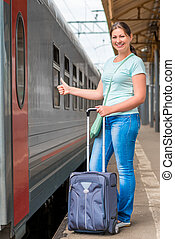 Satisfied girl with a suitcase waiting for a train at the...