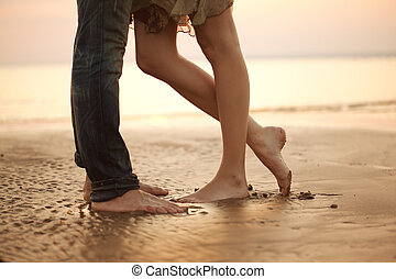 A loving young couple hugging and kissing on the beach....
