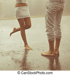 A loving young couple hugging and kissing under a rain...
