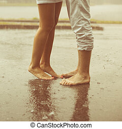 A loving young couple hugging and kissing under a rain....