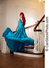 Young woman with luxurious long beautiful red hair in a blue fashionable evening dress  in the rich interior.