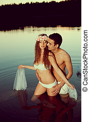 Two lovers in a lake at night. Girl and man at sunset in the...