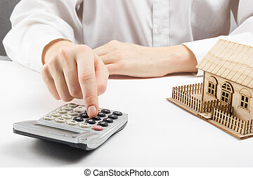 Real estate concept - businessman counting behind home architectural model