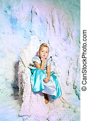 Little girl in princess dress on a background of a winter fairy tale. Baby snow queen. Smiling child snowy kingdom. Kid in in carnival costume.
