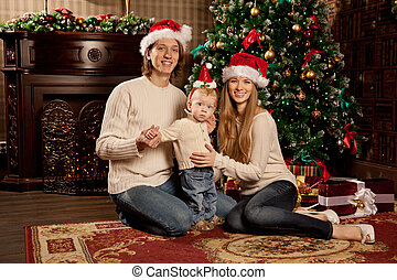 Happy smiling family near the Christmas tree celebrate New...