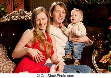 Happy smiling young family near the Christmas tree celebrate...