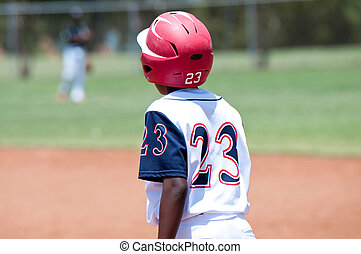 Young african american baseball boy on first base - Youth...