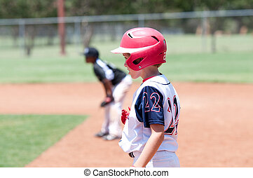 Young american baseball boy on first base - Youth baseball...