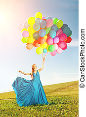 Luxury fashion woman with balloons in hand on the field...