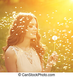 Beautiful young woman blowing dandelion. Trendy young girl...