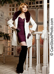 Beautiful adult woman in winter coat with fur. Trendy modern...