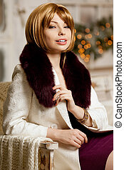 Beautiful adult woman in a winter coat with fur. Trendy...