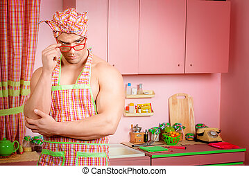 householder - Handsome muscular man in an apron cooking in...