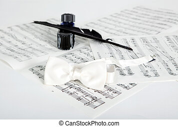 Ink bottle, feather, bow-tie and notes isolated on white
