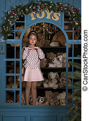 Girl portrays a porcelain doll in the window with plush...