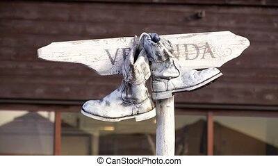Pair of old white boots hang on a wooden nameplate and...
