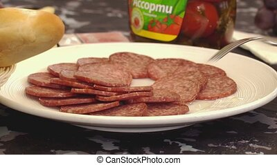 Someone takes salami from white big plate on a table by a...