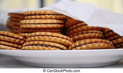 Many cookies with chocolate are lie in white plate covered...