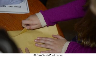 Girl's hands unpacking yellow envelope and give a paper with...