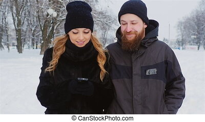 Bearded man and a woman using a smartphone