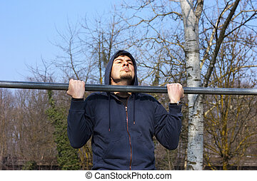 Chin-up Workout - A young adult male practicing strength...