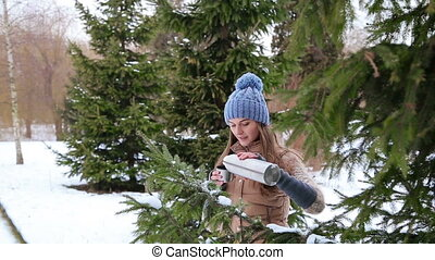 Beautiful girl drinking from a thermos near trees HD