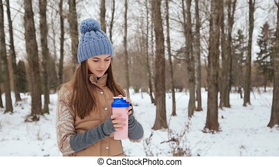 Beautiful girl with a shaker in the winter park