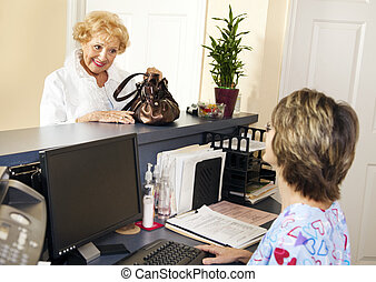 Patient Checks Out - Pretty senior patient checking out of...