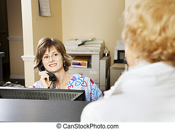 Receptionist Greets Patient - Receptionist in a doctor\'s...