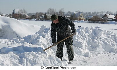 Man with a shove - A man in camouflage clothing removes snow...