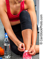 Fit woman sitting on floor and tie shoelace Bottle water on...