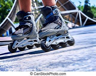 Girl riding on roller skates . - Kids feet wearing roller...