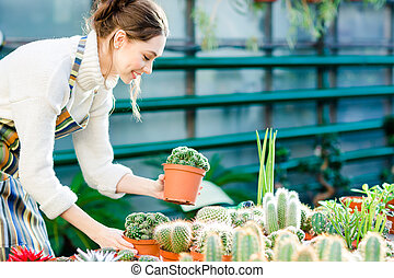 Happy cute young female gardener taking care of cactuses