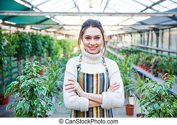 Beautiful happy young woman gardener in colorful striped...