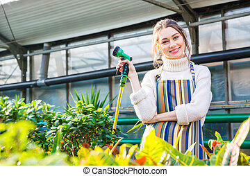 Smiling woman standing in orangery and holding garden hose -...