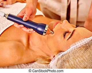 Young woman receiving electric facial massage. - Young woman...