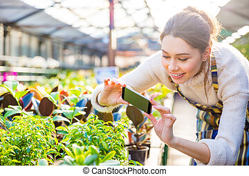 Happy woman gardener taking picture of plants with...