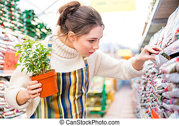 Pensive woman gardener on shopping in garden store - Closeup...