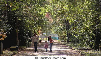 Mother with little girls walking in the park